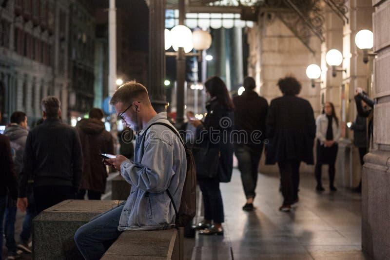 Ung vit man som använder hans smartphone på natten i Belgrade, en kvinna som gör samma i bakgrunden arkivbilder