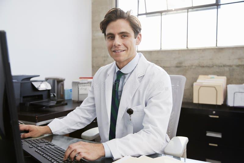 Ung vit manlig doktor som använder datoren som ler till kameran royaltyfri bild
