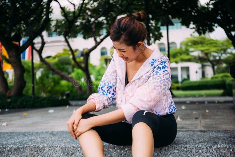 Ung vuxen asiatisk kvinna som har knäleden att smärta olycka på att jogga fotografering för bildbyråer