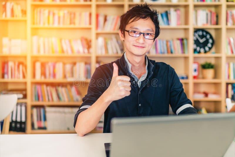 Ung vuxen asiatisk man med bärbara datorn, tummar upp ok tecken-, inrikesdepartementet- eller arkivplats, med kopieringsutrymme,  fotografering för bildbyråer