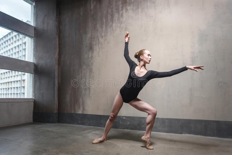 Ung vuxen ballerina som repeterar hennes klassiska dans i en idrottshall arkivbilder