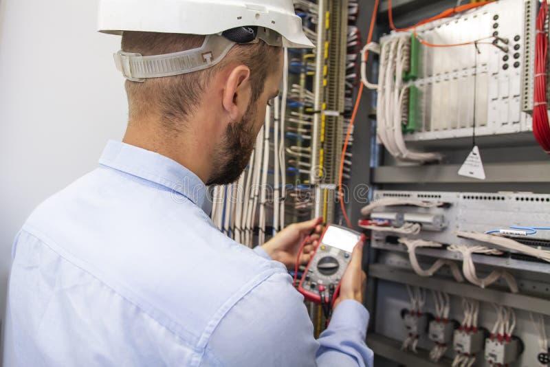 Ung vuxen elektrikerbyggmästaretekniker som kontrollerar elektrisk utrustning i fördelningssäkringsask arkivfoto