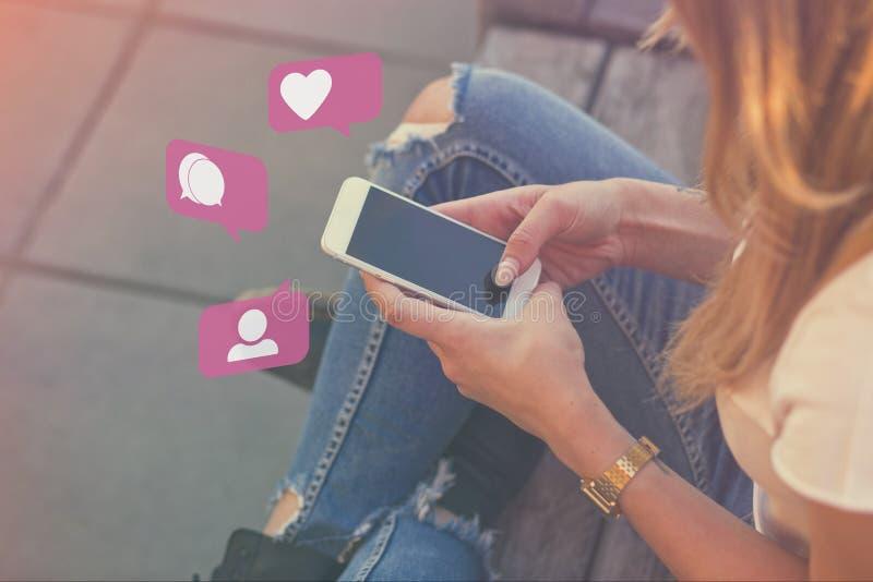Ung vuxen flicka Influencer som använder socialt massmedia på Smartphone på utomhus-, likt, anhängare, kommentarbubblasymboler fotografering för bildbyråer