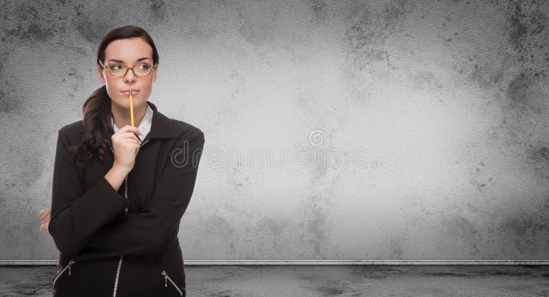 Ung vuxen kvinna med blyertspennan och exponeringsglas som framme står av den Grungy tomma väggen för mellanrum med kopieringsutr arkivfoton