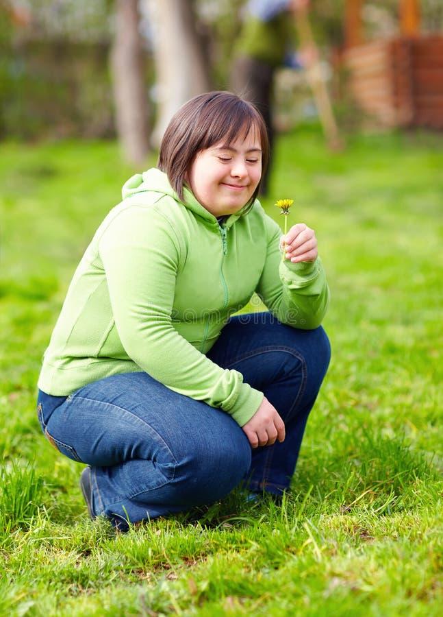 Ung vuxen kvinna med handikapp som tycker om naturen i vårträdgård fotografering för bildbyråer