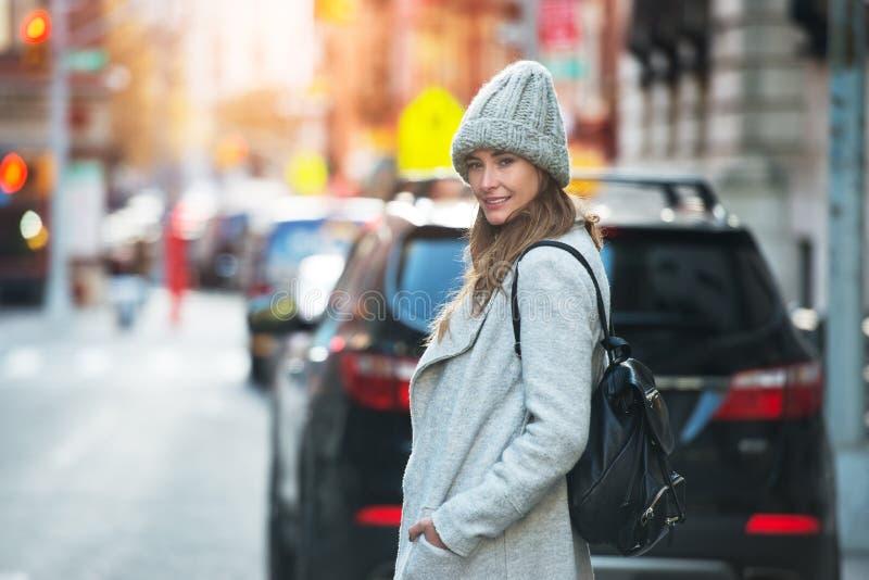Ung vuxen kvinna som går på den bärande hatten och omslaget för stadsgata med ryggsäcken arkivbilder