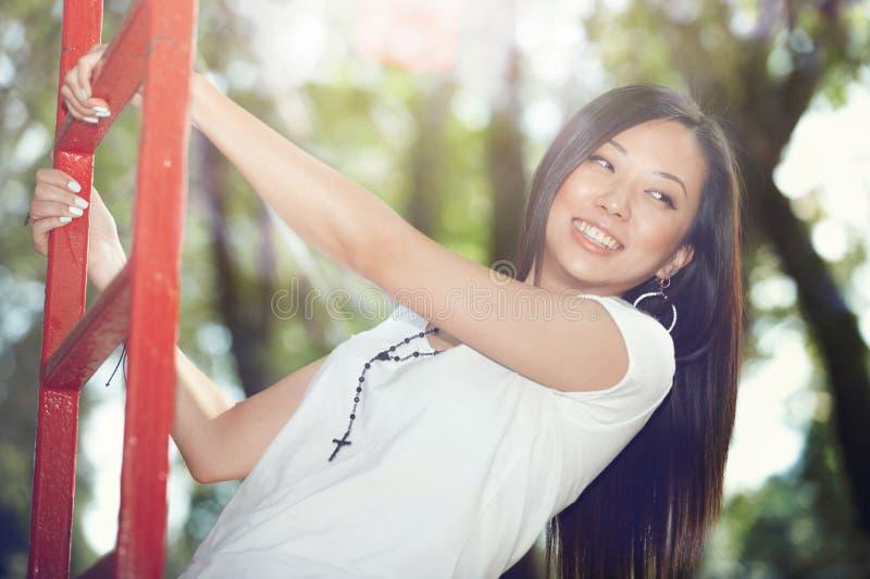 Ung vuxen kvinna som har gyckel på lekplatsen arkivbilder