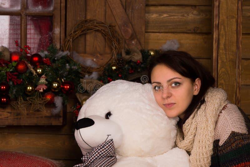Ung vuxen kvinna som kramar dockan för vit björn arkivbild
