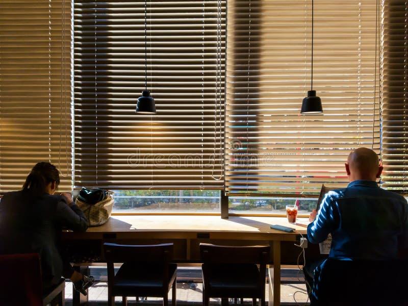 Ung vuxen människatjänsteman som arbetar eller kopplar av på coffee shopkafét, listenning musik som läser tidningen, Hipsterstil, arkivfoto