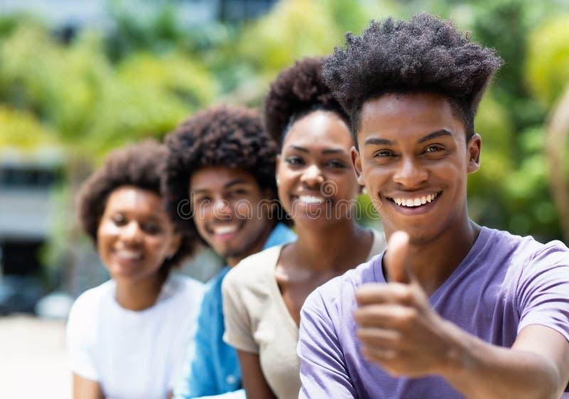 Ung vuxen man för afrikansk amerikan med vänner som visar upp tummen royaltyfri fotografi