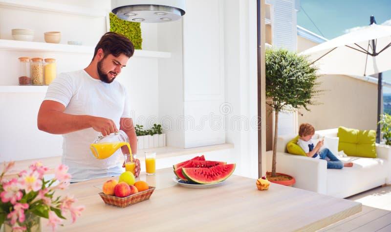 Ung vuxen man, fader som häller ny fruktsaft, medan stå i öppet utrymmekök på en solig sommardag arkivbild