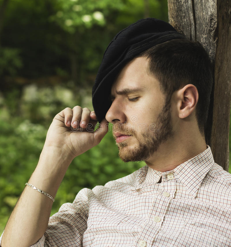 Ung vuxen man med att vila för lock som är utomhus- fotografering för bildbyråer