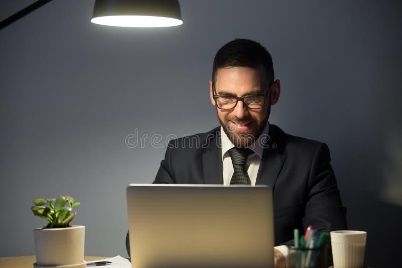 Ung vuxen man som sent arbetar på bärbar datordatoren på natten arkivfoton