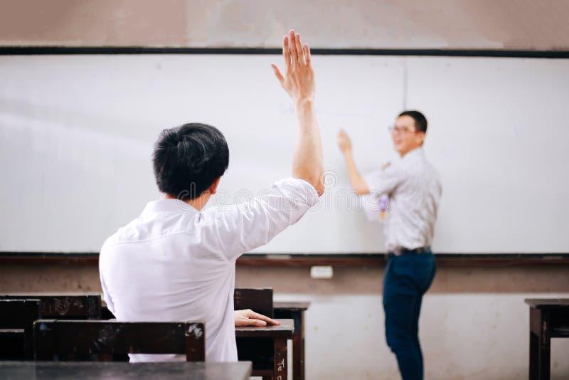 Ung vuxen manlig student som lyfter händer upp i luften för att fråga frågor från en annan manlig lärare royaltyfri bild