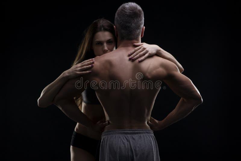 Ung vuxen muskulös man och kvinna Sexiga par på svart bakgrund royaltyfria bilder