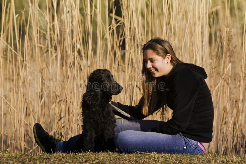 Ung vuxen Sitting med henne hund arkivfoton