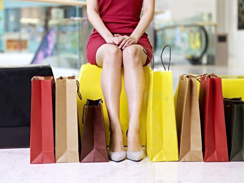 Ung woman& x27; s-ben och färgrika shoppingpåsar arkivbild
