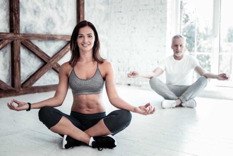 Ung yogalärare som tycker om yogaperiod i grupp fotografering för bildbyråer