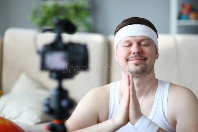 Ung yogaman som antecknar sportbloggen på kamera arkivbilder