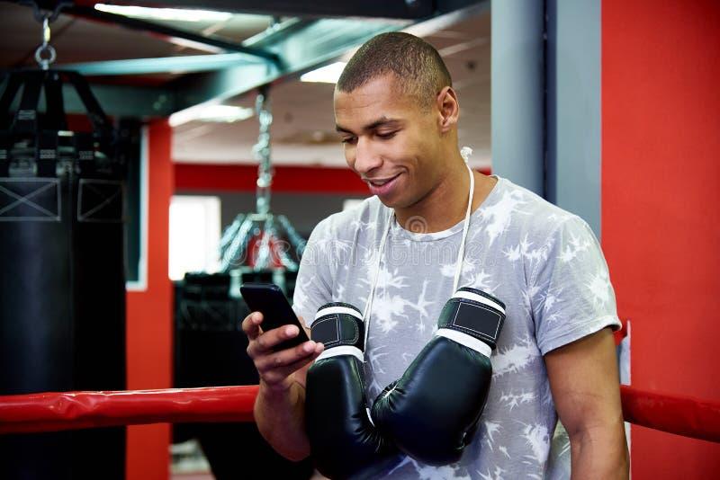 Ung yrkesmässig boxare med en telefon i cirkeln på bakgrund av idrottshallen med påsar arkivbild