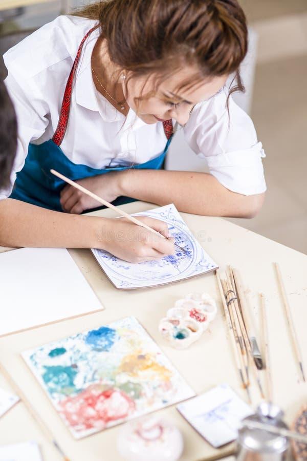 Ung yrkesmässig kvinnlig Ceramistfönsterrutor och målningkeramik arkivbilder
