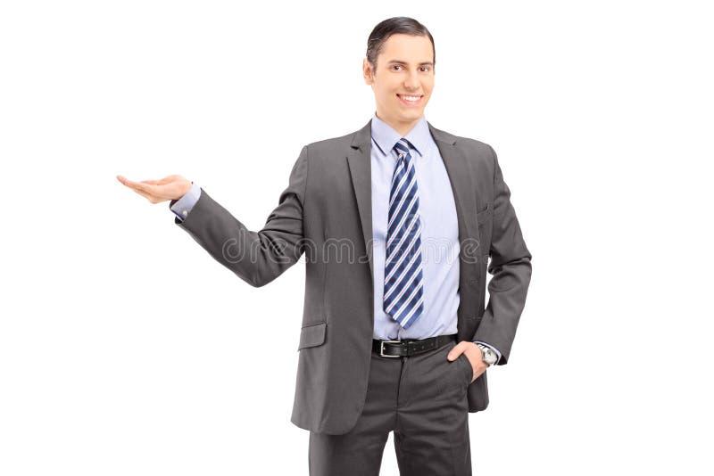 Ung yrkesmässig man i en dräkt som gör en gest med hans hand