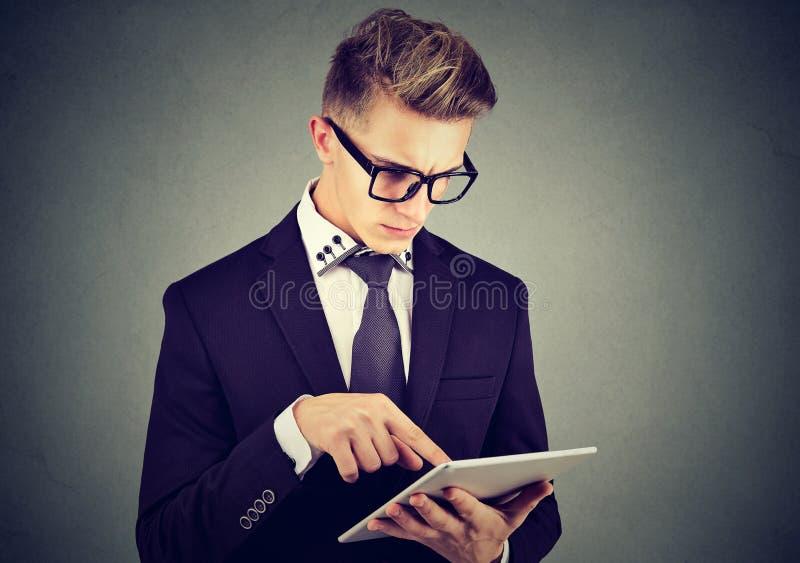 Ung yrkesmässig man som använder en minnestavlaPC royaltyfri fotografi