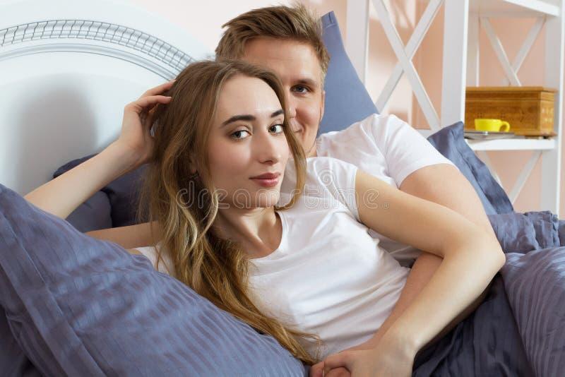 Unga älska härliga par i sängen arkivfoto