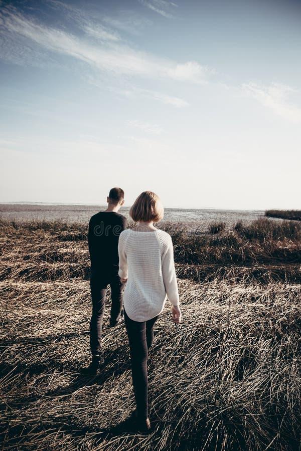 Unga älska par av tonåringar rymmer händer och promenerar Get royaltyfri fotografi