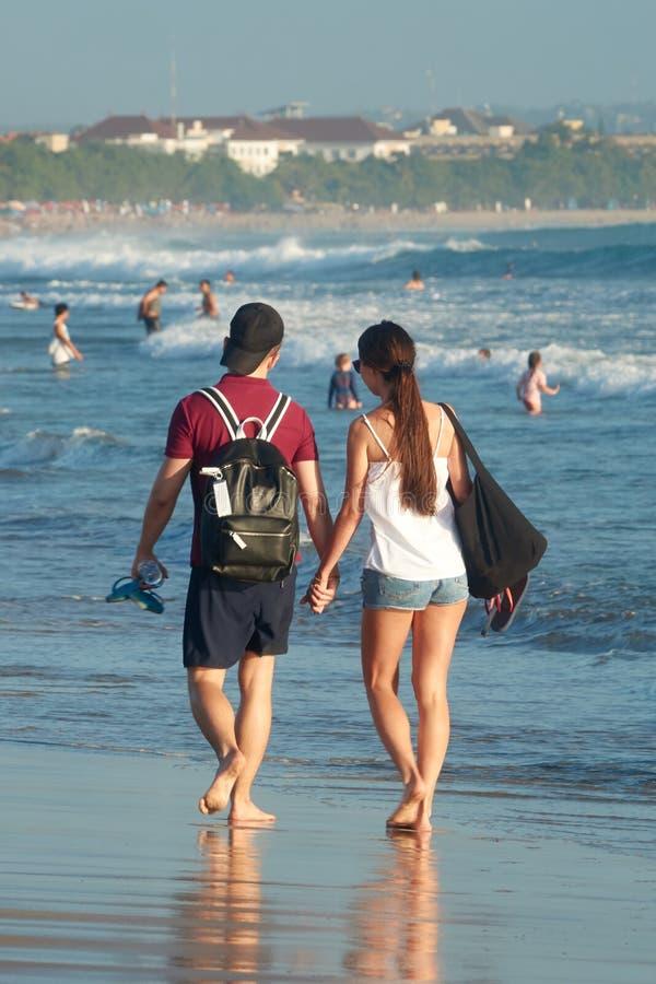 Unga älska par som går på en strand längs ett hav i deras bröllopsresa royaltyfria foton