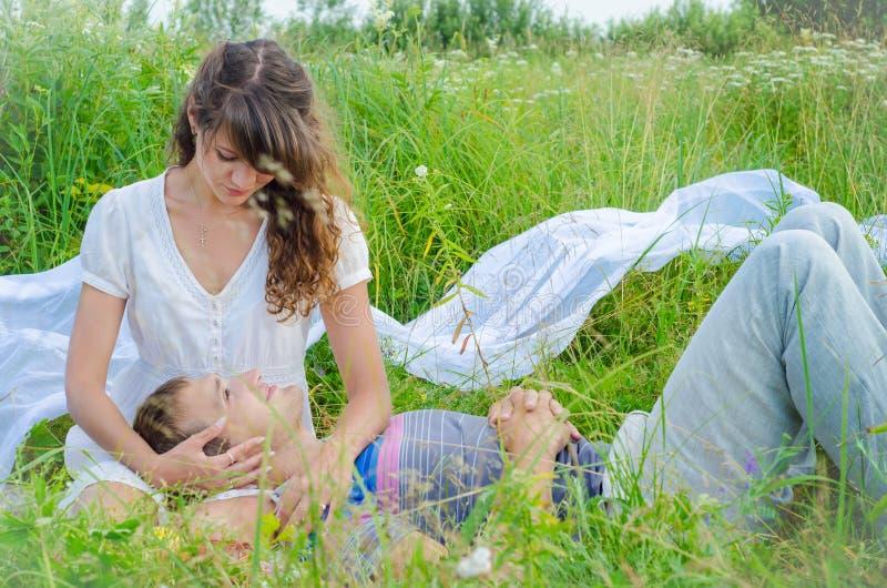 Unga älska par som omfamnar i gräset royaltyfri fotografi