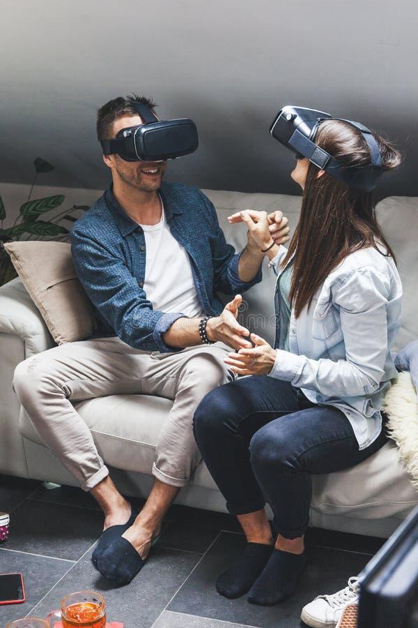 Unga älska par som spelar videospelvirtuell verklighetexponeringsglas arkivfoto