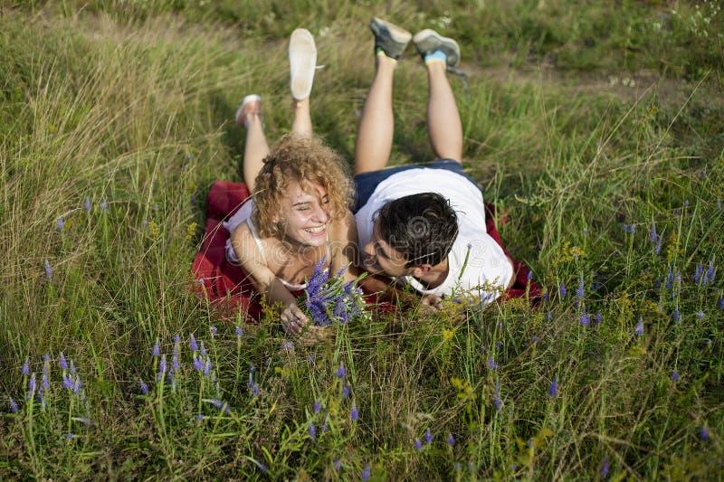 Unga älska par som tycker om naturen, rymmer händer och går på fältet med lavendel Härligt folk på naturen i vår på arkivfoto