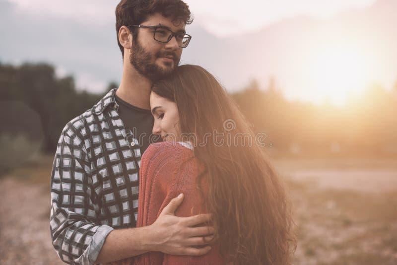 Unga älska par som utomhus kramar arkivfoto