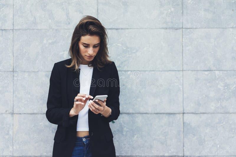 Unga affärskvinnor för stående i svart dräkt genom att använda smartphonen som isoleras på den konkreta gråa väggmodellen för bak royaltyfri foto