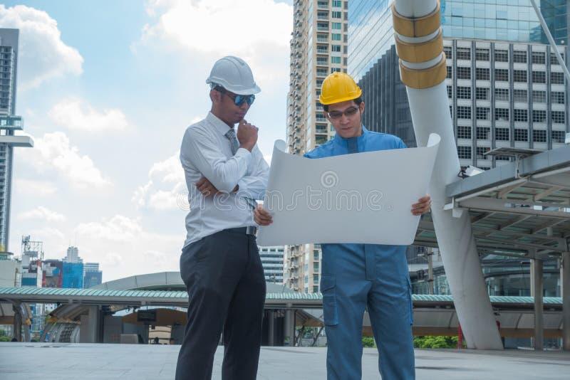 Unga affärsmän och teknikerer som analyserar mest projest konstruktion royaltyfria foton