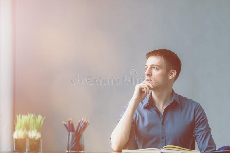Unga affärsmancaucasians som sitter på skrivbordkontorstabellen och tar anmärkningar i anteckningsbok Se ut fönstret på det vänst arkivfoton