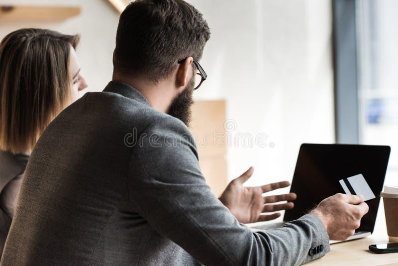 unga affärspartners med kreditkorten som ser bärbara datorn royaltyfria foton
