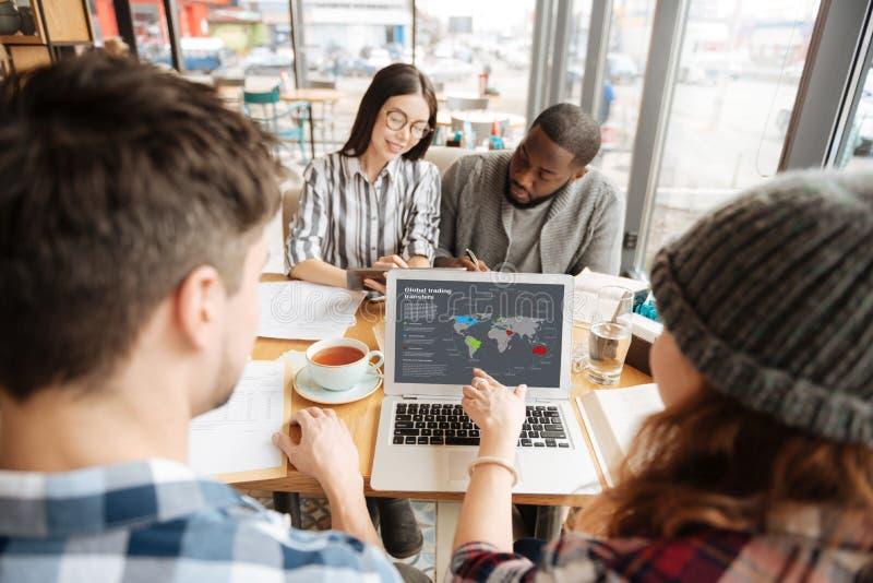 Unga affärspartners som använder bärbara datorn på kafét arkivbilder