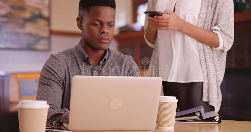 Unga afrikansk amerikanmillennials som meddelar, medan arbeta på datoren och smsa royaltyfri bild