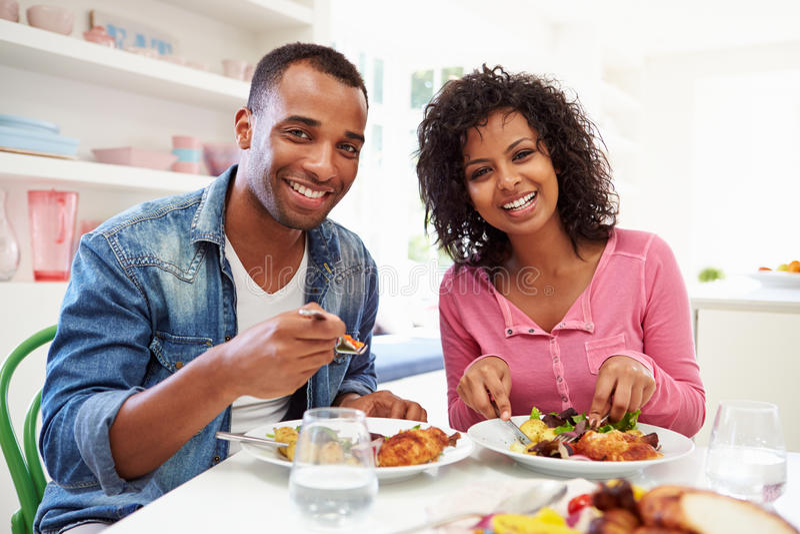 Unga afrikansk amerikanpar som hemma äter mål royaltyfri fotografi