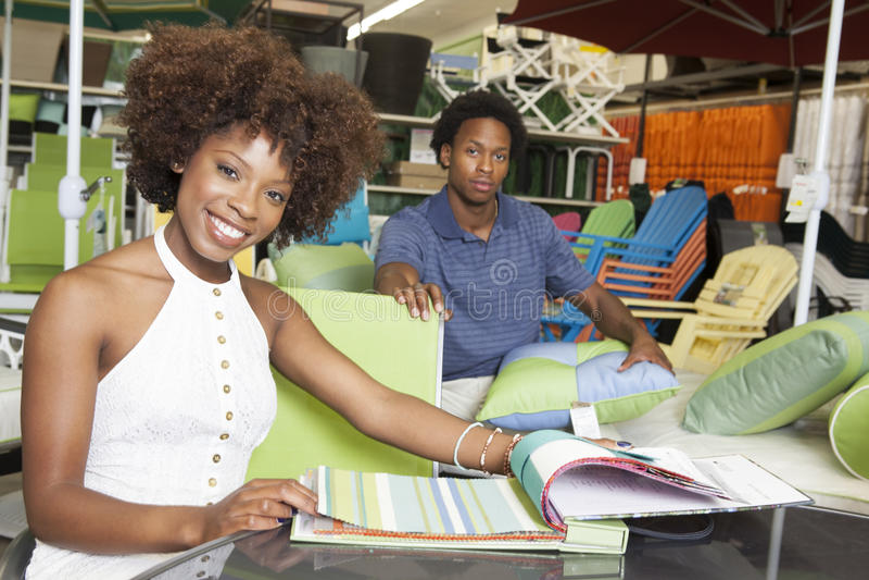 Unga afrikansk amerikanpar som köper utomhus- möblemang på lagret royaltyfri bild