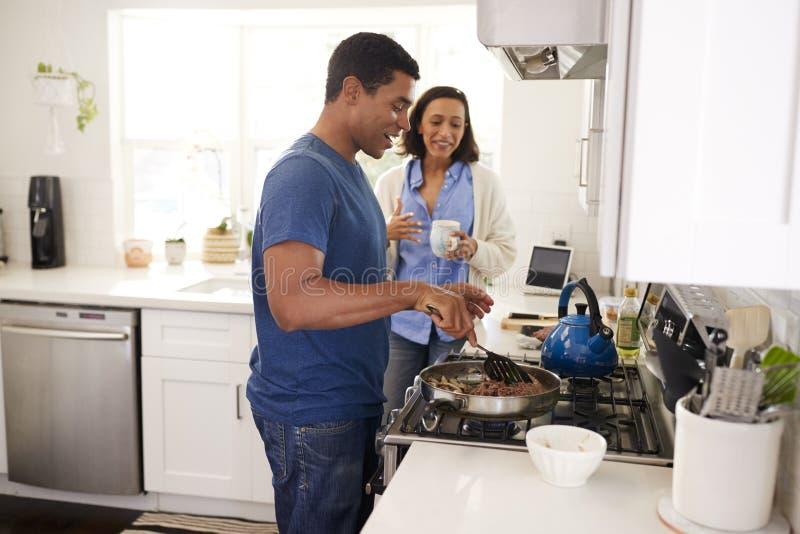 Unga afrikansk amerikanpar som står i köket, man som lagar mat upp mat i en panna på hoben, slut, selektiv fokus, sidosikt royaltyfria foton