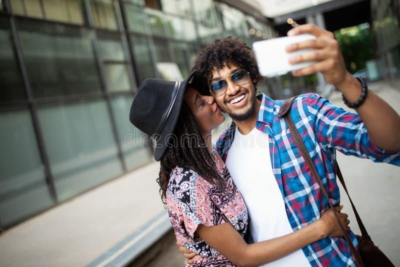 Unga afrikanska par poserar f?r ferieselfie i stad royaltyfri foto