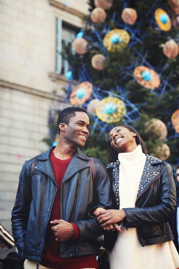 Unga afrikanska par som är förälskade med härliga leenden som poserar mot julgranen med garneringar under att gå utomhus i winte royaltyfri fotografi