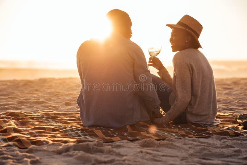 Unga afrikanska par som håller ögonen på en strandsolnedgång och dricker vin royaltyfri foto