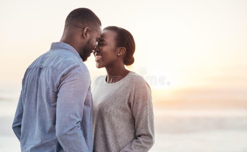 Unga afrikanska par som tycker om ett romantiskt ögonblick på stranden royaltyfri bild