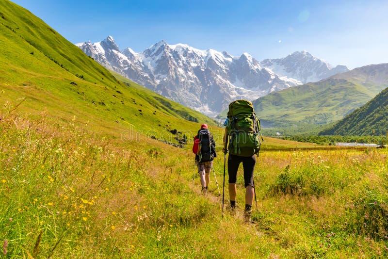 Unga aktiva flickor som fotvandrar i större Kaukasus berg, Mestia område, Svaneti, Georgia fotografering för bildbyråer
