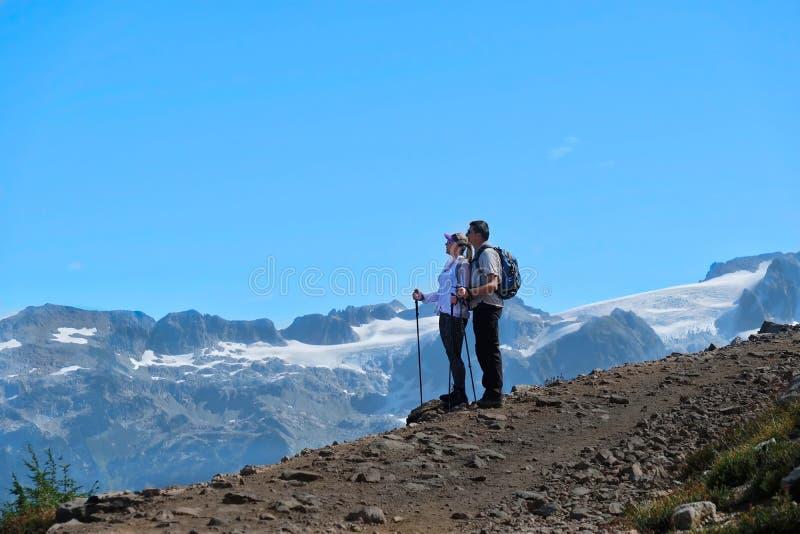 Unga aktiva par som fotvandrar i berg i Stillahavs- nordvästligt royaltyfria bilder