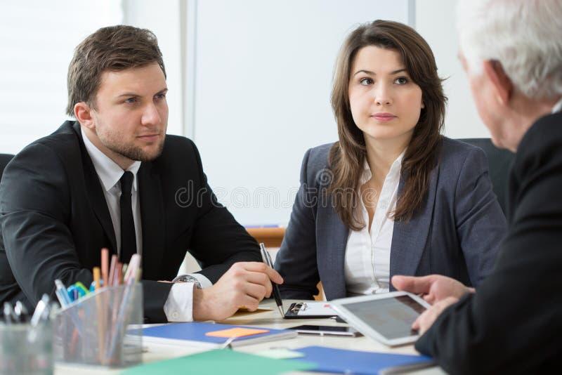 Unga anställda som talar med framstickandet arkivbild